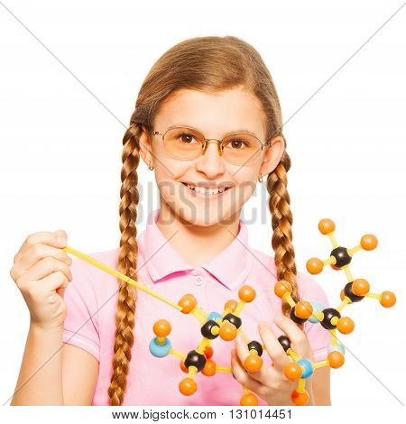 Cute young girl in glasses with two long plaits, pointing to molecular model, isolated on white