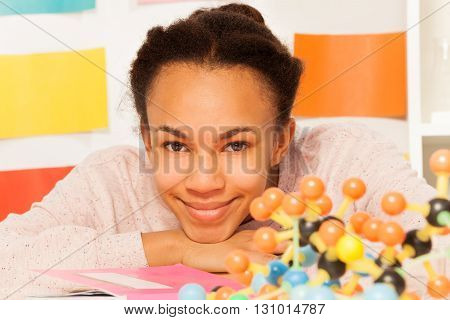 Portrait of teenage African schoolgirl with molecular structure at the desk in chemistry laboratory