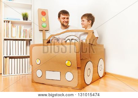 Father and his son driving handmade cardboard car at the room