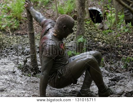 STOCKHOLM SWEDEN - MAY 14 2016: Man covered with mud falling in the obstacle race Tough Viking Event in Sweden April 14 2016