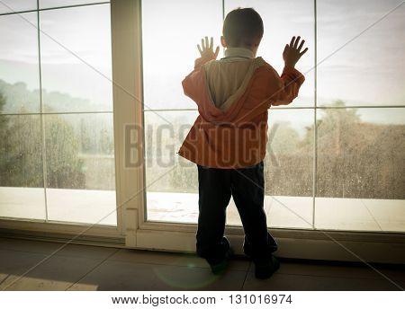 A little boy looking trough the window