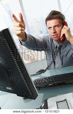 Empresario serio hablando por teléfono fijo teléfono gesticular de foto sentado en el escritorio de oficina.