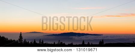 Looking at inspirational landscape ocean view beautiful sunset from Tenerife island. Panoramic view with mountains on islands and clouds over ocean and sunset sky on Tenerfie Canary Islands Spain.