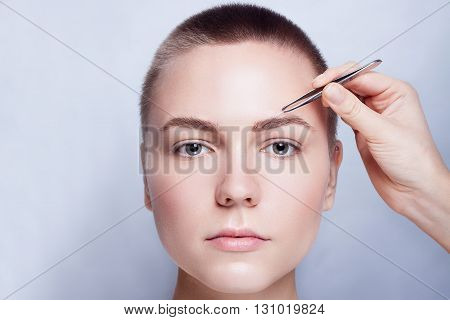 Young woman with short hair plucking eyebrows with tweezers close up studio snimak. on a light background. beauty shot .Closeup part of face woman plucking eyebrows depilating with tweezers.