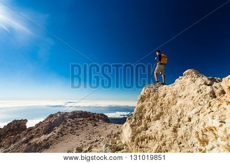 Man tourist hiker or trail runner looking at beautiful inspirational landscape in high mountains. Male runner with backpack happiness and enjoying inspiring view on rocky top of mountain Spain.