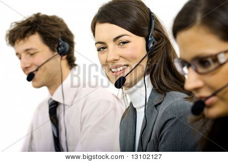 Young customer service representatives sitting in a row and talking on headset, smiling. Isolated on white background.