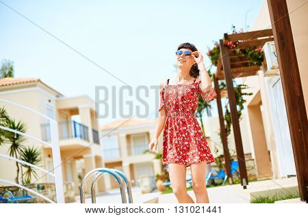 young woman standing near the pool. woman wearing in red dress and sunglass.
