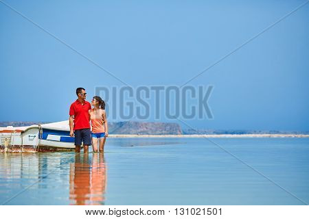 couple standing in the sea near the boat.