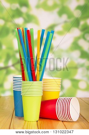 Bright disposable paper cups and straws on abstract green background.