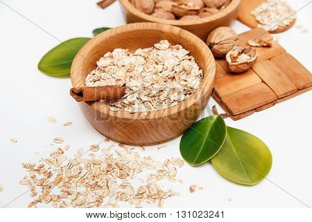There are Walnuts and Rolled Oats in the Wooden Plates with Sticks of Sinnamon,Wooden Support,Spoon,Green Leaves,Healthy Fresh Organic Food on the White Background