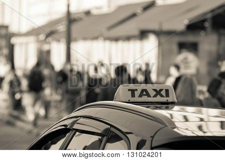 symbol or sign with an inscription of a taxi is located on a car roof on an indistinct background street of sepia color