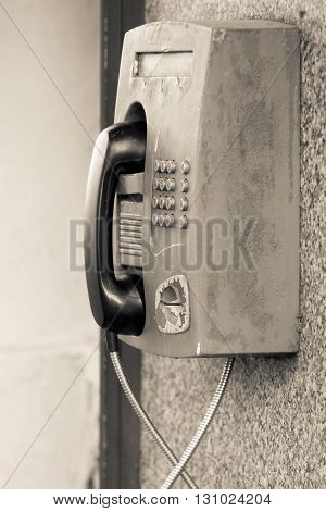 the big old payphone of sepia color a closeup and located outdoor on a wall