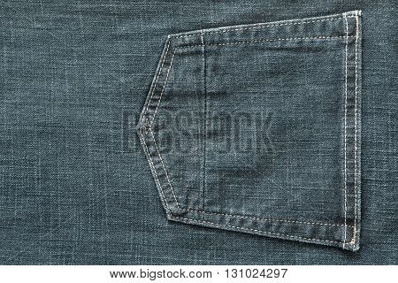 fragment of trousers from jeans material or jeans clothes with the big sewn pocket closeup for the textile textured background of pale indigo color