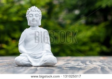 Zen yoga and meditation concept. White Buddha on green relax background.