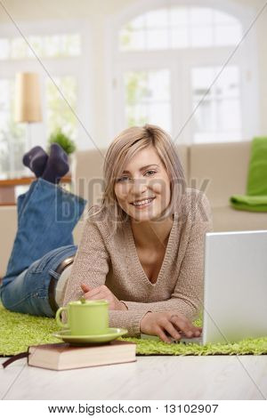 Attraktive junge blonde Frau auf Boden zu Hause im Wohnzimmer Surfen im Internet auf Laptop comp