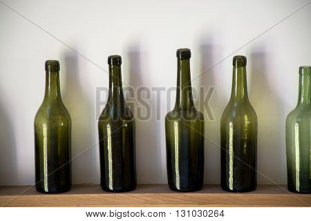 Old dark green Normandy cider and calvados bottles on traditional farm background
