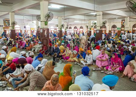 Amritsar, India - March 29, 2016: Unidentified indian people eating free food in the temple premises of Sikh Golden Temple in Amritsar, India