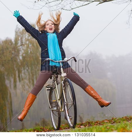 Happy carefree active woman having fun riding bike bicycle in fall autumn park. Crazy young girl relaxing. Healthy lifestyle and recreation leisure activity. poster