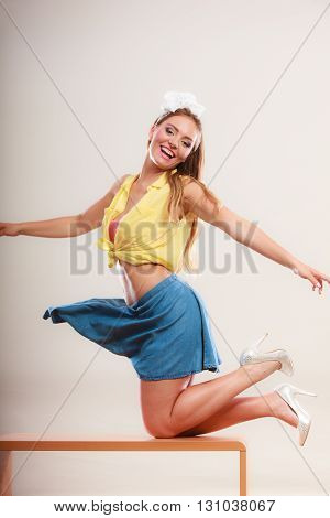 Alluring seductive pretty pin up girl wearing hairband bow skirt and high heels. Attractive gorgeous young retro woman dancing on table.