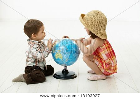 Little kids crouching on floor playing with globe over white background.
