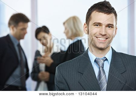Portrait of happy businessman with coworkers talking in the background.