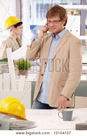 Junge Architekt stehen Schreibtisch, talking on Mobile Phone.