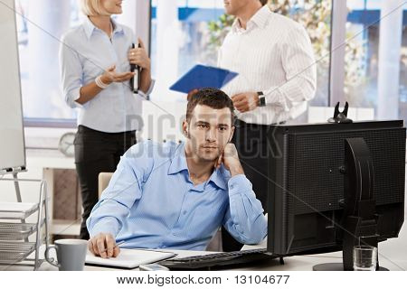 Young businessman working on computer at office desk.