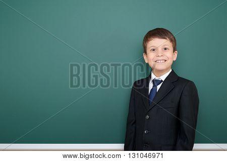 happy successfull school boy in black suit portrait on green chalkboard background, education concept