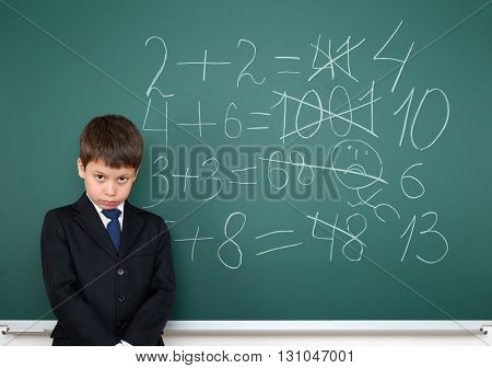 school boy decides examples math incorrect on chalkboard background, education concept