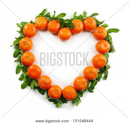 Colorful orange tangerines positioned in a heart shape with mint sprigs underneath it on a white background, top view