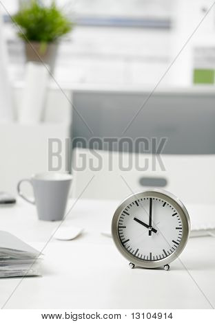 Close-up photo of clock on office desk.