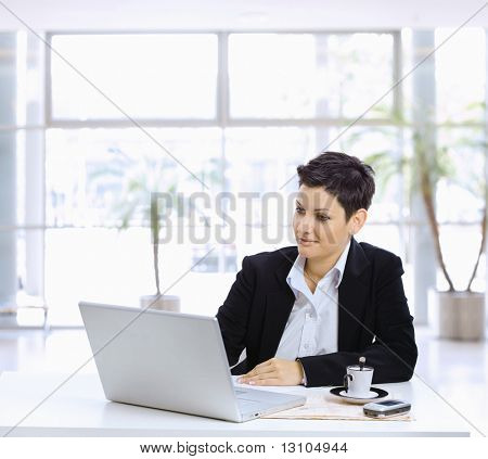 Businesswoman sitting at table in office lobby, using laptop computer, looking at screen.