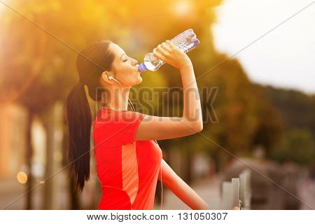 Young woman drinking water after running in the city. Female fitness model training outside in Prague.