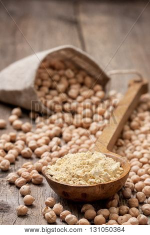 Chickpea flour in a wooden spoon chickpeas on old wooden background