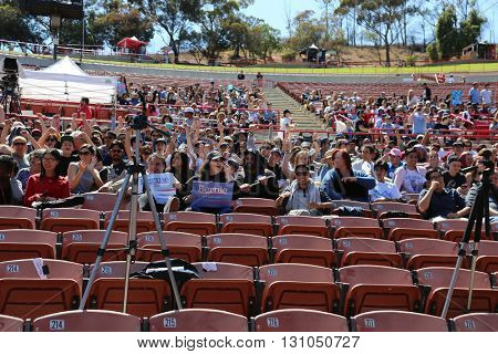 IRVINE, CALIFORNIA - May 22: Fans Smile and Wave Signs as they wait in the stadium of the Irvine Meadows Amphitheater for Bernie Sanders at a Rally in Irvine, California on May 22, 2016