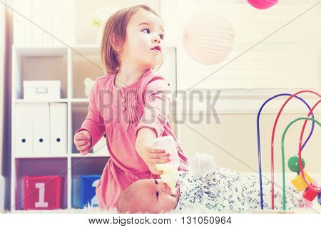 Happy Toddler Girl Feeding Her Baby Sister