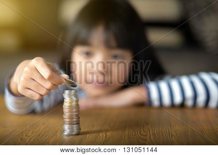 Little girl counts his coins on a table Select focus at coins
