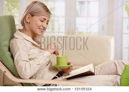 Woman sitting in armchair, reading book, holding coffee mug, smiling.