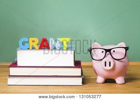 Education Grant Theme With Pink Piggy Bank On Top Of Books With Chalkboard In The Background