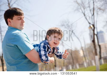 Son on fathers at the park having fun together