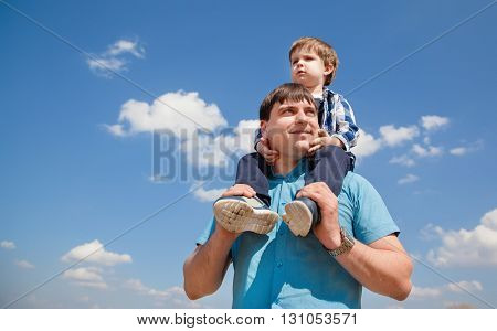 Young father and a little son on a sky background