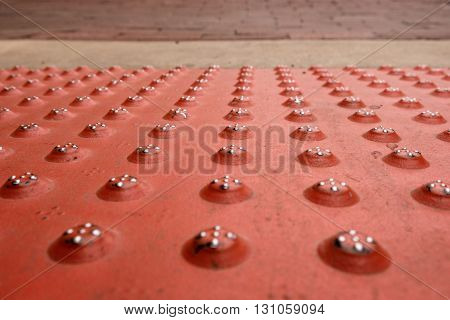 Red steel sidewalk plate with round pattern, leading to cement and bricks