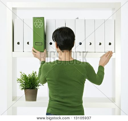 Conceptual image of environmental conservation, woman working in green office.