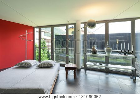 Interior of a studio apartment, double bed, red wall