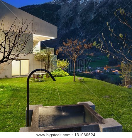 Architecture, concrete house with stone fountain, night scene