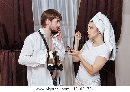 Morning couples. Husband and wife are going to the party. Man talking on the phone and holding her shoes. Girl doing make-up with a towel on her head. Family time.