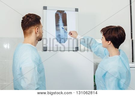 two yound doctors examining a x-ray film at the diaphanoscope.