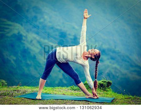 Vintage retro effect hipster style image of woman doing Ashtanga Vinyasa yoga asana Utthita trikonasana - extended triangle pose outdoors