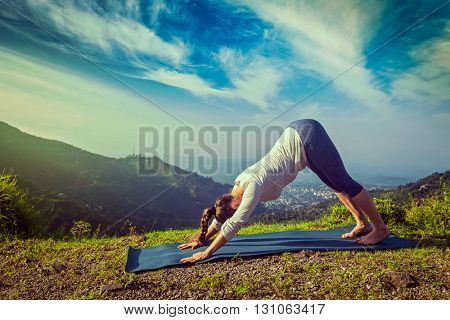 Vintage retro effect hipster style image of young sporty fit woman doing yoga asana Adho mukha svanasana - downward facing dog - in Surya Namaskar Sun Salutation outdoors in Himalayas in the morning