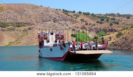 Siverek Turkey - July 22 2012: Transportation of cars and passengers at Siverek - Kahta. Departure ferry with passengers and cars at Siverek - Kahta in Turkey.